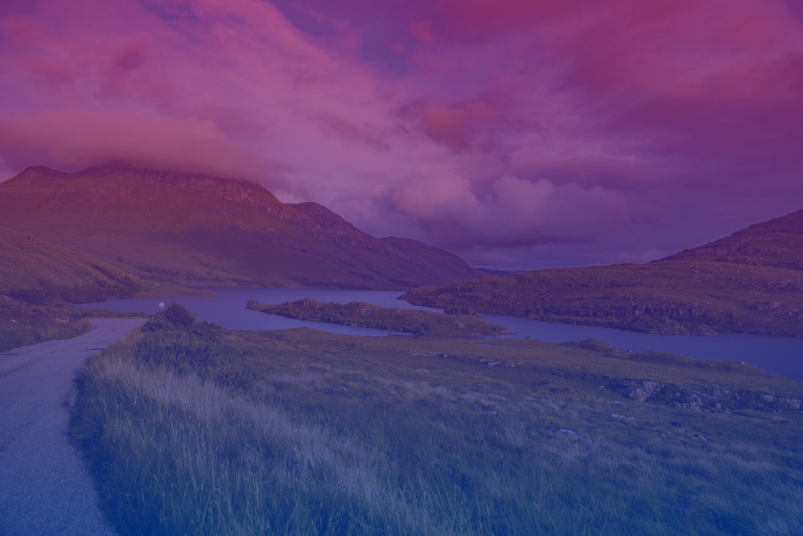A picture of Scottish hills on a cloudy day with the bi flag colours over them